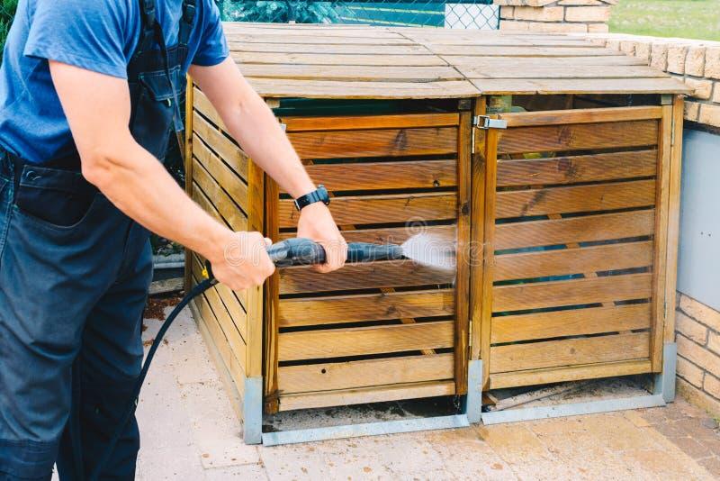 Immondizia di legno sporca di pulizia del giardino con un cleane ad alta pressione fotografia stock libera da diritti