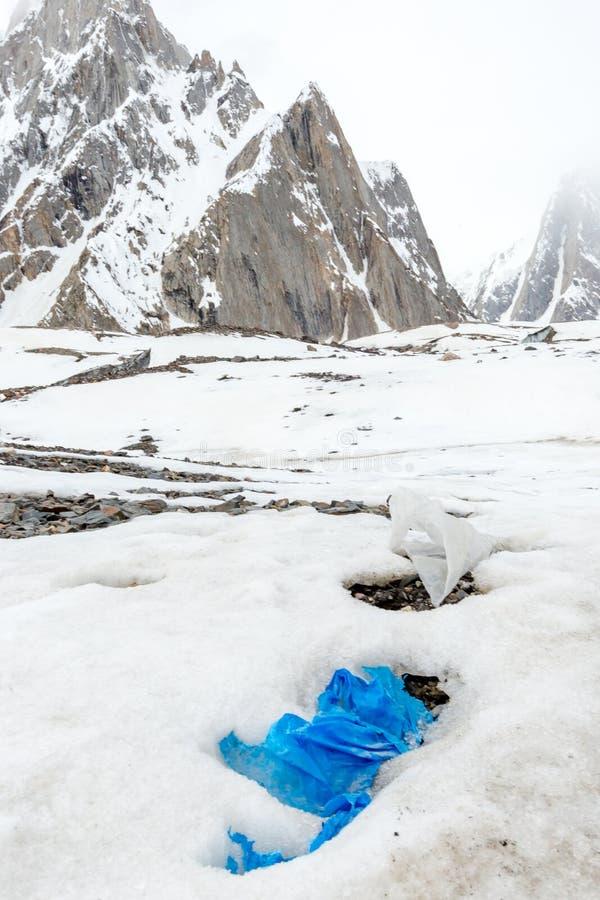 Immondizia sparsa sopra la montagna nevosa Conserviamo il pianeta e ricicliamo l'immondizia in eccesso fotografia stock