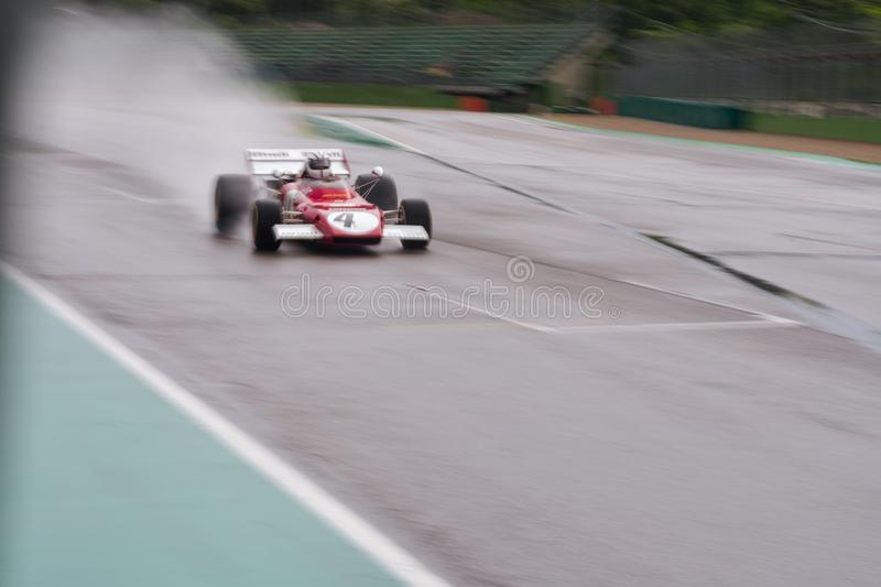 Imola, Italy 28 April 2019: vintage formula one car is flying on a wet track, panning photo. Vintage formula one car is flying on a wet track, panning photo stock photography