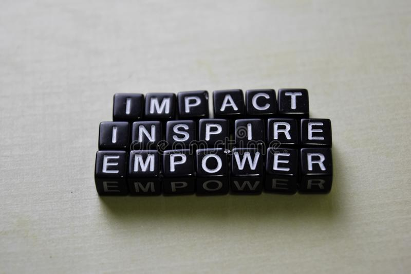 Impact - Inspire - Empower on wooden blocks. Business and inspiration concept stock image