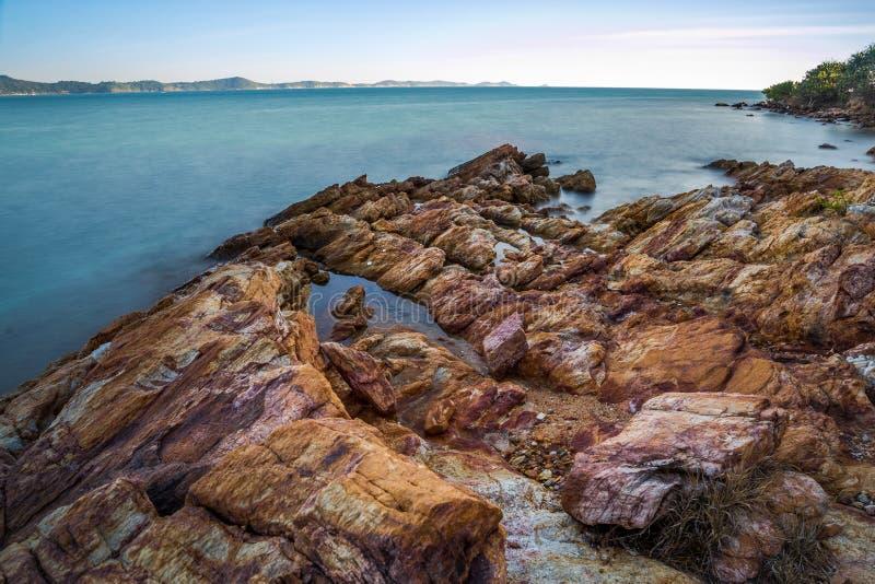 Impacto da onda do mar com raia da rocha como uma água da fervura com céu claro fotografia de stock