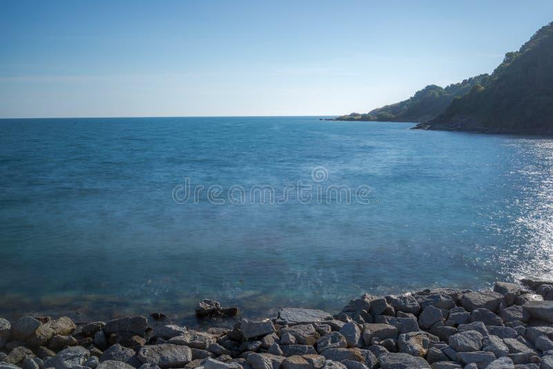Impacto da onda do mar com raia da rocha como uma água da fervura com céu claro foto de stock