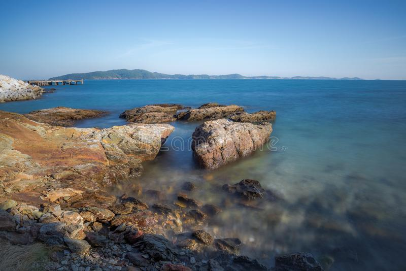 Impacto da onda do mar com raia da rocha como uma água da fervura com céu claro imagem de stock