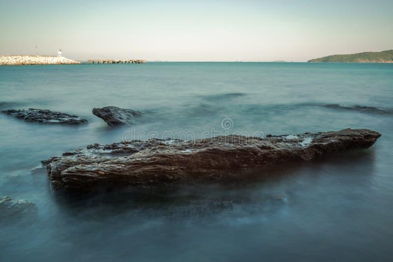 Impacto da onda do mar com raia da rocha como uma água da fervura com céu claro imagens de stock