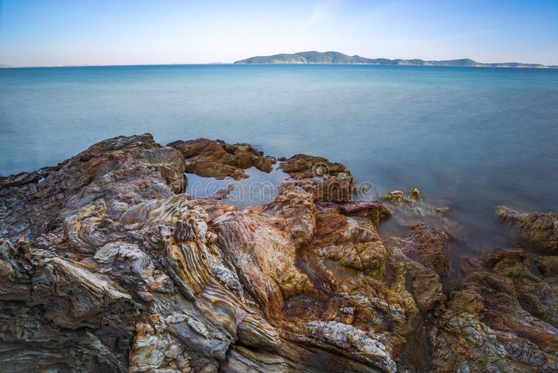 Impacto da onda do mar com raia da rocha como uma água da fervura com céu claro imagens de stock royalty free