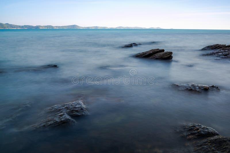 Impacto da onda do mar com raia da rocha como uma água da fervura com céu claro fotos de stock