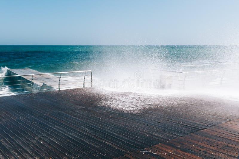 Impacto das ondas contra o passeio imagens de stock