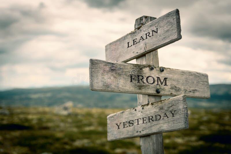 Impari dal testo di ieri sull'aria aperta di legno del cartello in natura fotografia stock