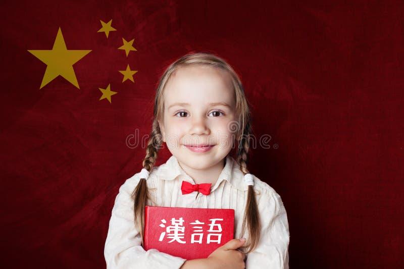 Impari la lingua cinese Studente astuto del bambino sulla bandiera cinese immagine stock