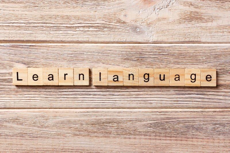 Impari la parola di lingua scritta sul blocco di legno Impari il testo sulla tavola, concetto di lingua immagini stock