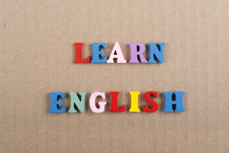 IMPARI la parola INGLESE su fondo di carta composto dalle lettere di legno di ABC del blocchetto variopinto dell'alfabeto, copi l immagine stock libera da diritti