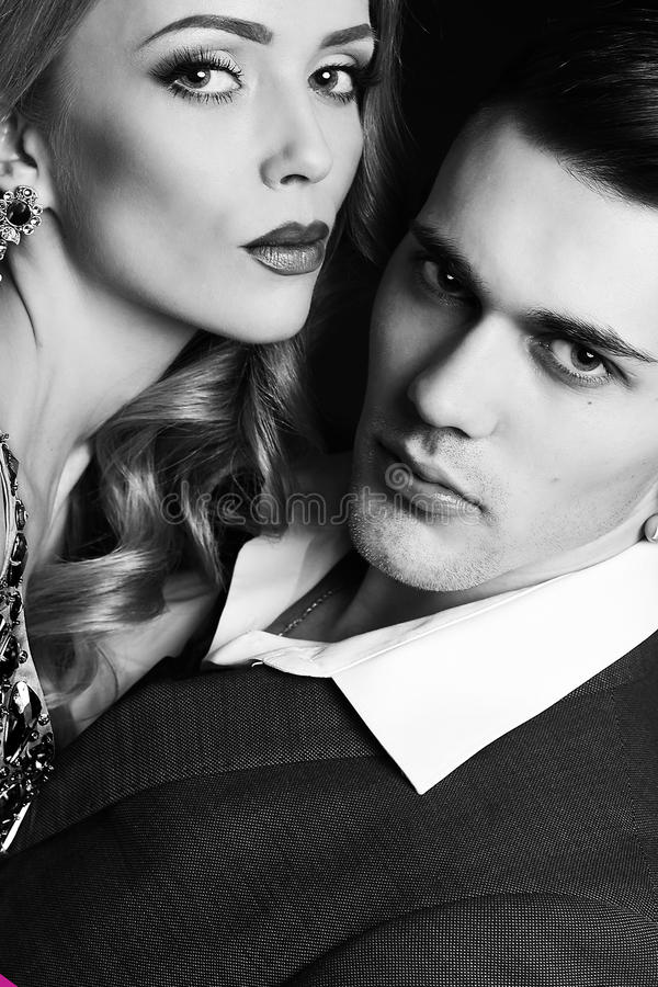 Impassioned couple. handsome businesslike men with beautiful girl with long blond hair. Fashion studio photo of impassioned couple. handsome businesslike men royalty free stock image