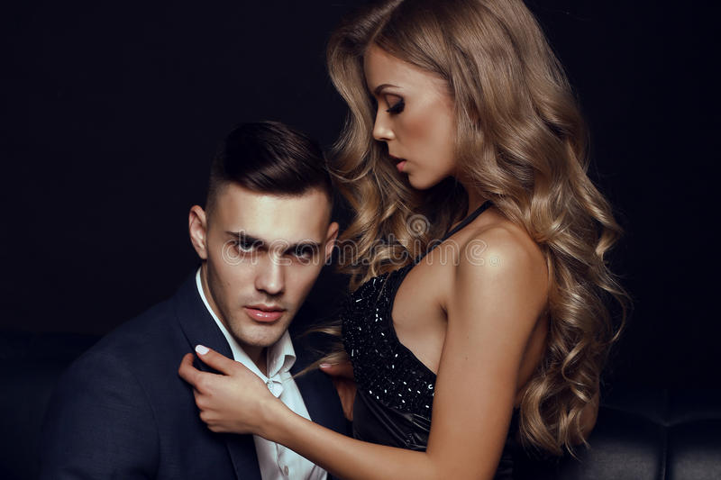 Impassioned couple. handsome businesslike men with beautiful girl with long blond hair. Fashion studio photo of impassioned couple. handsome businesslike men royalty free stock photo