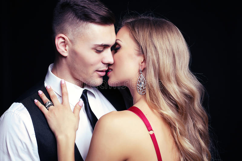 Impassioned couple. handsome businesslike men with beautiful girl with long blond hair. Fashion studio photo of impassioned couple. handsome businesslike men stock photos