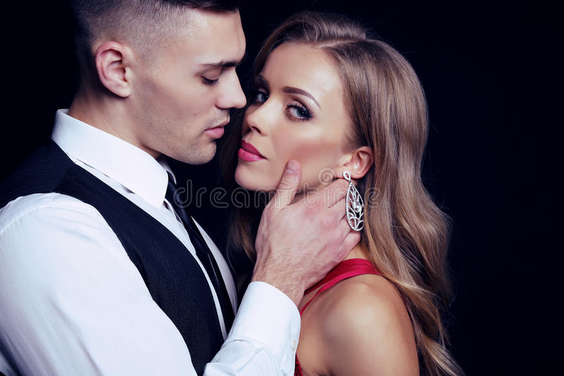 Impassioned couple. handsome businesslike men with beautiful girl with long blond hair. Fashion studio photo of impassioned couple. handsome businesslike men royalty free stock images