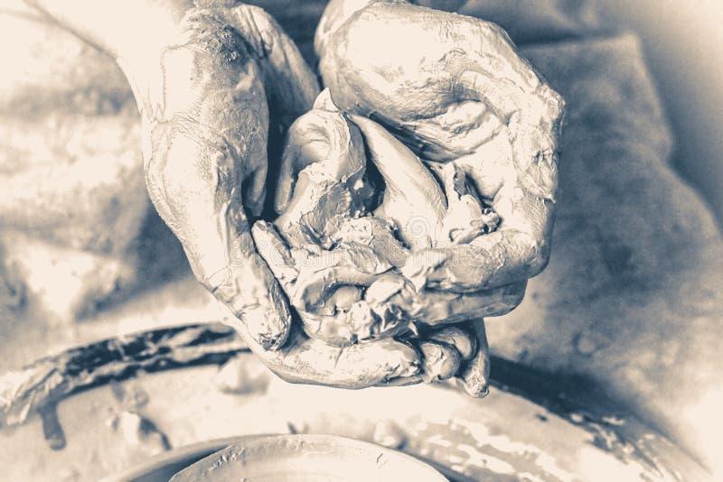 Impasti, argilla del raminanie nelle mani dell'uomo Vecchio stile d'annata fotografia stock