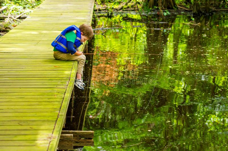An Impatient Fishing Boy Stares At His Still Bobber As He Leans stock photography
