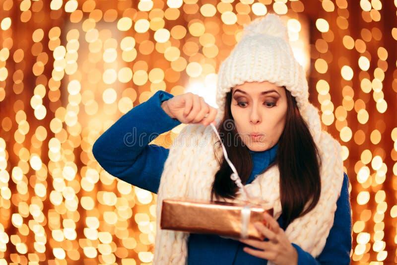 Funny Woman Opening Christmas Present Celebrating Winter Holidays stock photo