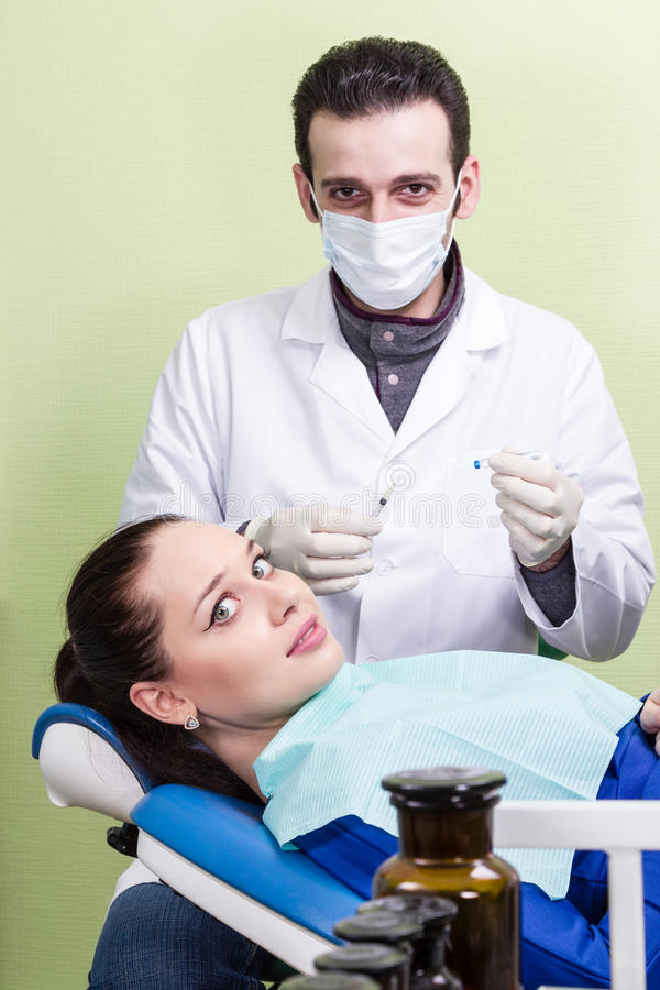 Impaurito paziente l'iniezione del dentista fotografie stock
