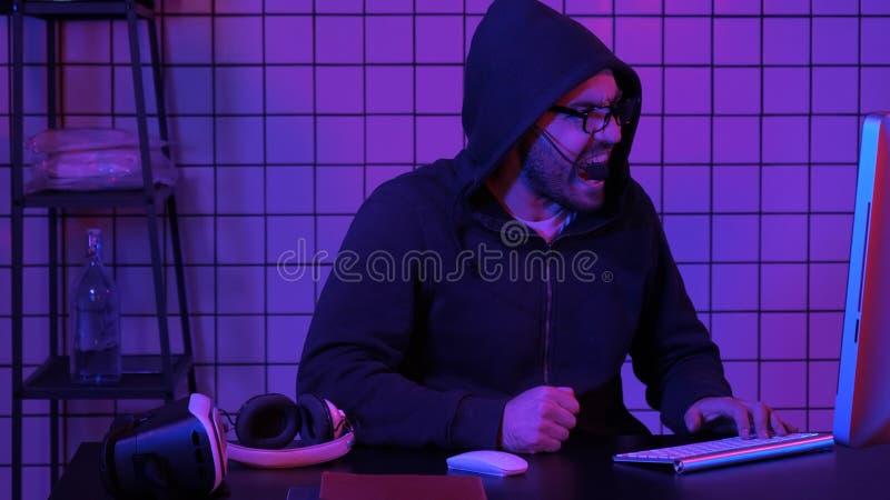 Impazziree di grida del Gamer della sconfitta nel video gioco che colpisce tavola con il suo pugno immagine stock libera da diritti