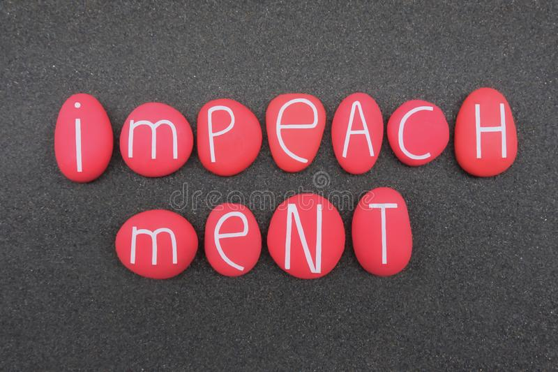 Impeachment text composed with red colored stone letters over black volcanic sand royalty free stock photo