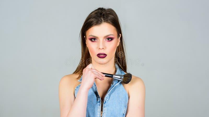 Imperfezioni nascondentesi Apparire bello e ritenere sicuro Labbra scure di trucco Donna attraente che applica la spazzola di tru fotografia stock