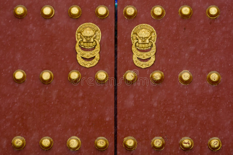 Imperial Palace Door. View of a gilt lacquered red door during a snow fall in Beijing, China royalty free stock image