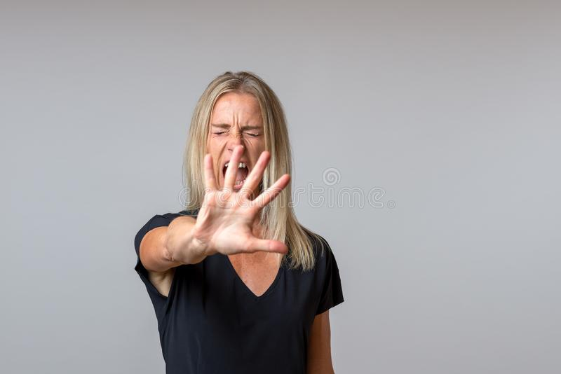Imperious arrogant woman gesturing with her hand. In a dismissive gesture while screaming royalty free stock photography