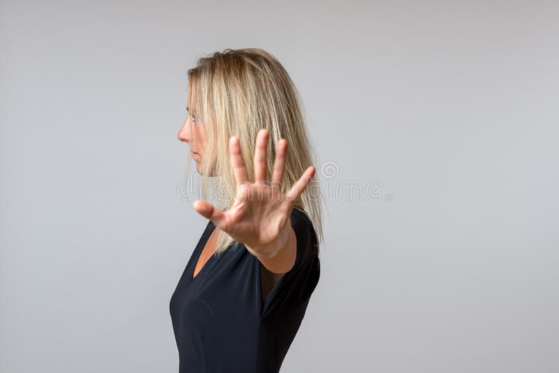 Imperious arrogant woman gesturing with her hand. In a dismissive gesture while turning to the e royalty free stock photos