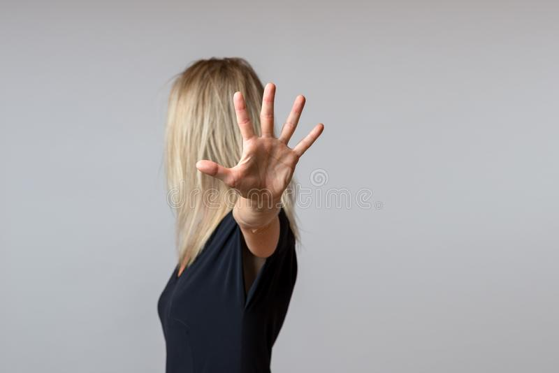 Imperious arrogant woman gesturing with her hand. In a dismissive gesture while turning away isolated on grey with copy space stock photo