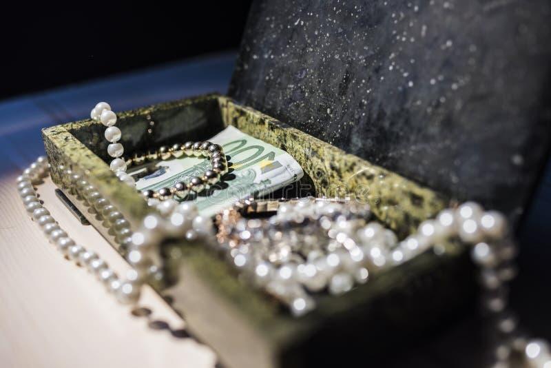 Imperli, braccialetto dell'oro e soldi in una scatola fotografie stock