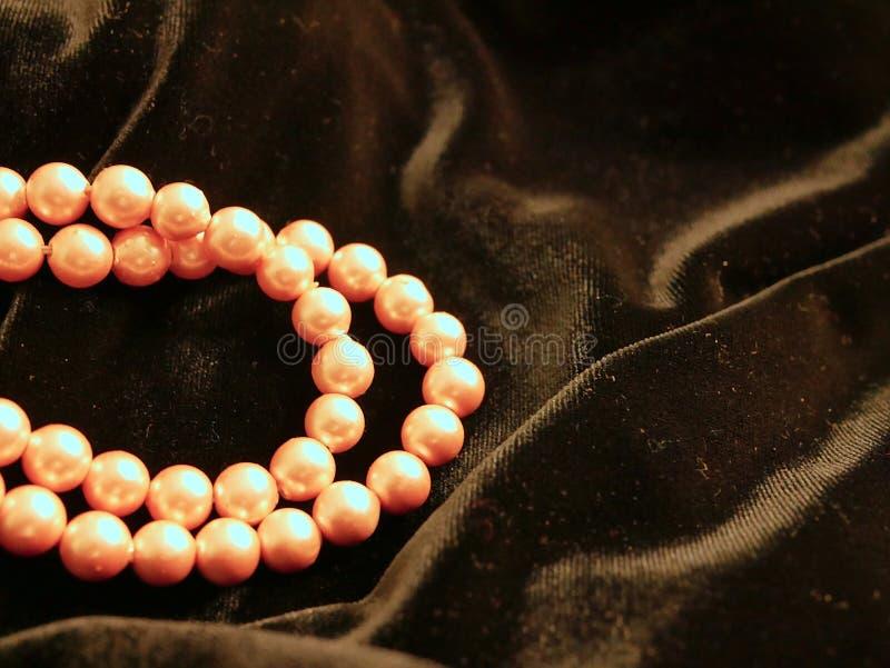 Imperli i gioielli della collana sul fondo nero del raso per il giorno di biglietti di S. Valentino immagini stock