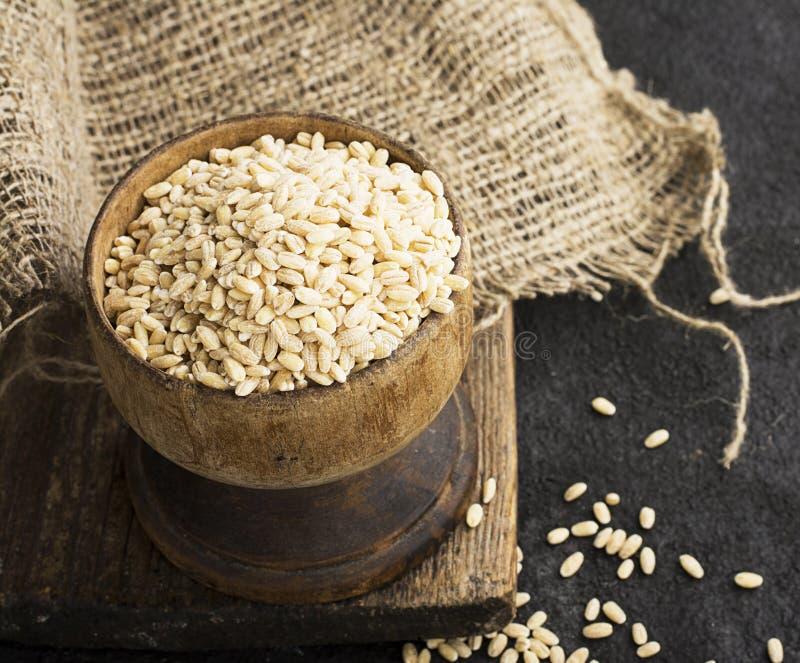 Imperli il cereale asciutto in una ciotola di legno d'annata su un fondo scuro normale per la disposizione e la pubblicità del te fotografie stock