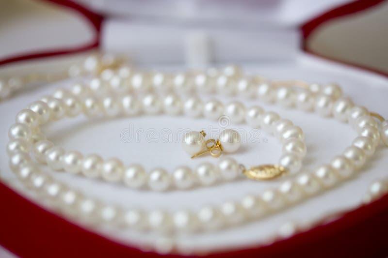Imperli la collana e gli orecchini in contenitore di regalo rosso fotografia stock libera da diritti