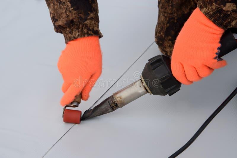 Imperméabilisation et isolation au chantier de construction, procédé de cachetage de toit de membrane synthétique avec l'outil de photo stock