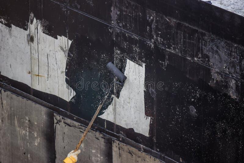 Imperméabilisation, travailleur peignant le mur en béton extérieur avec du goudron i photographie stock