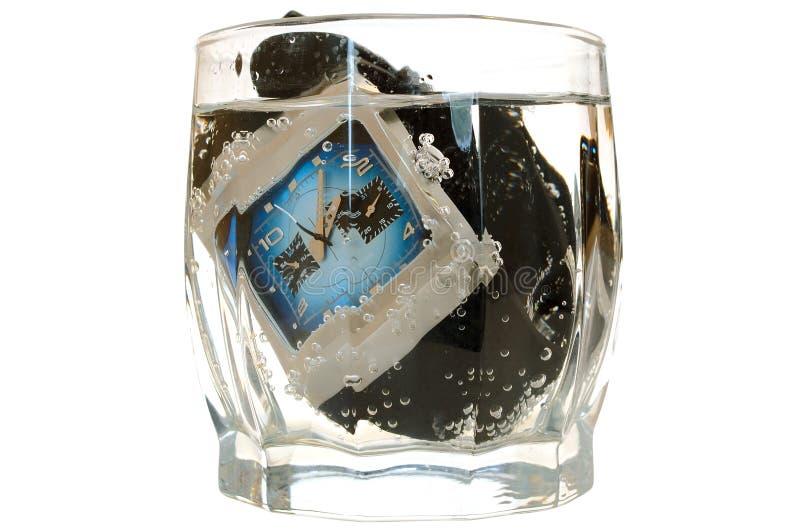 Impermeabilice el reloj en vidrio con agua. imagenes de archivo