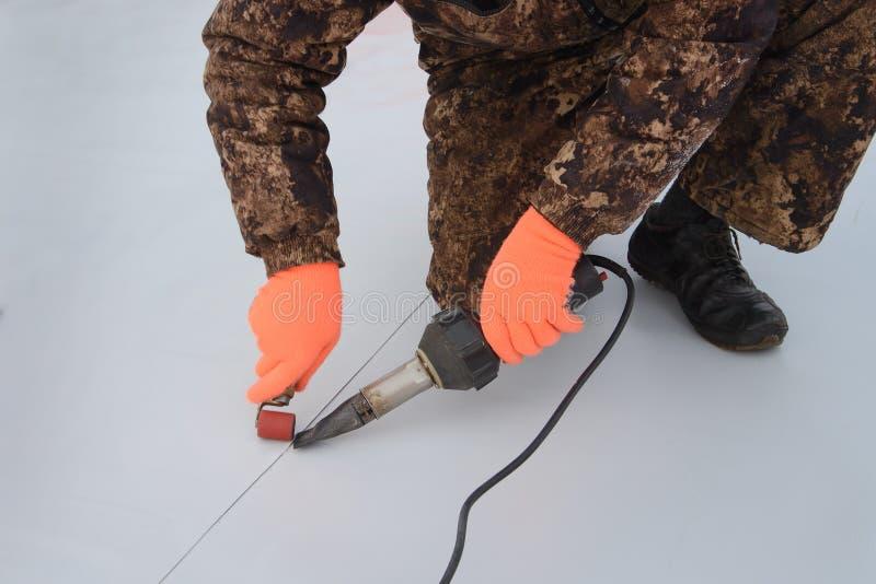 Impermeabilizzando ed isolamento al cantiere, processo di sigillamento del tetto della membrana sintetica con gli attrezzi per br immagini stock