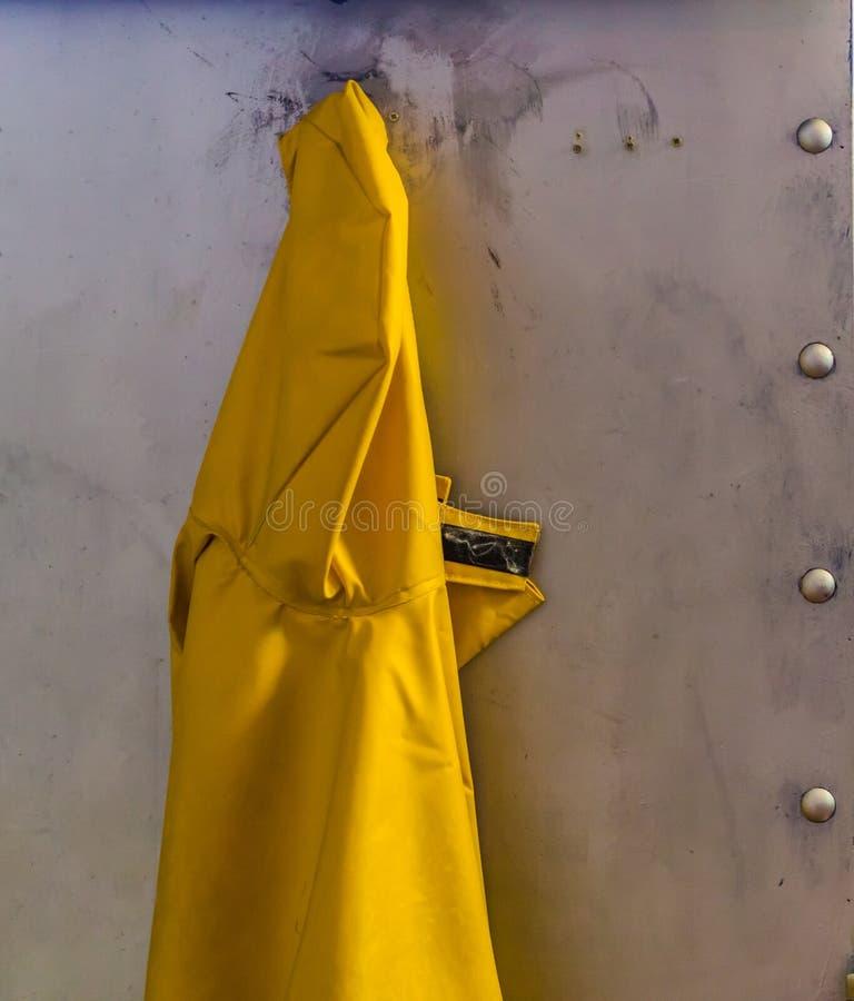 Impermeable amarillo que cuelga en una pared del metal, fondo marino, ropa protectora por días lluviosos imágenes de archivo libres de regalías