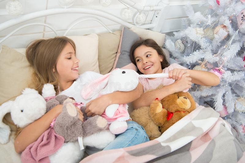 Impertinente e sveglio Le piccole ragazze combattono sopra i giocattoli Piccoli bambini attivi a letto all'albero di Natale Picco immagini stock