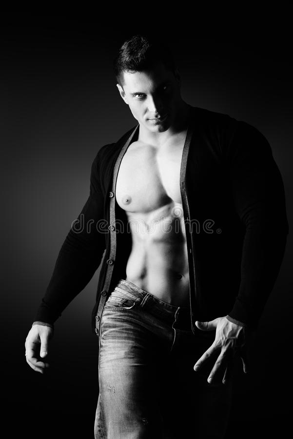 Impetuous man. Portrait of a muscular young man posing over dark background stock images