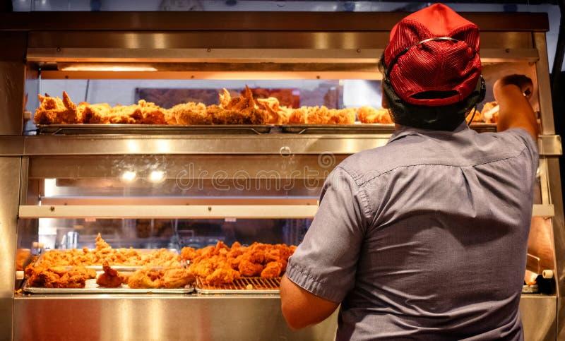 Impianti degli impiegati del salario minimo in una cucina degli alimenti a rapida preparazione fotografie stock