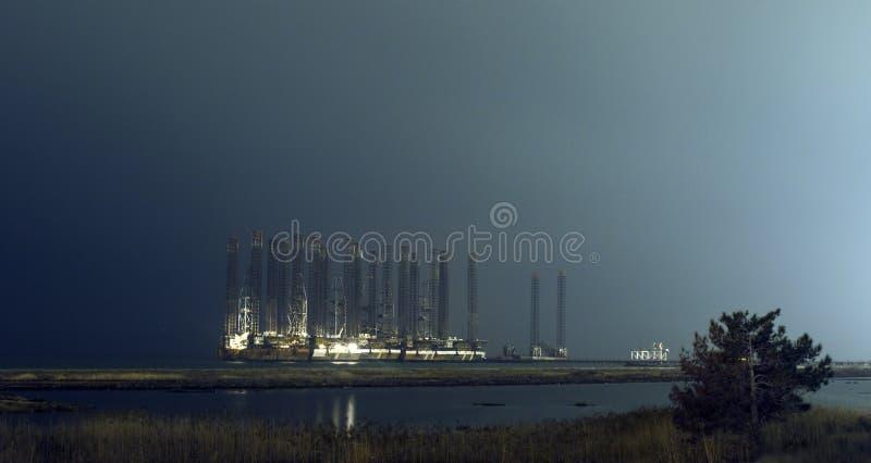 Impianto di perforazione del petrolio marino alle acque basse alla notte Bacu, Azerbaigian Spiaggia di Shikhov immagini stock libere da diritti