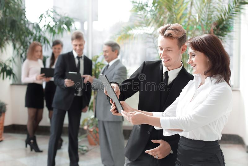 Impiegati della società con le lavagne per appunti che stanno nell'ingresso dell'ufficio fotografia stock
