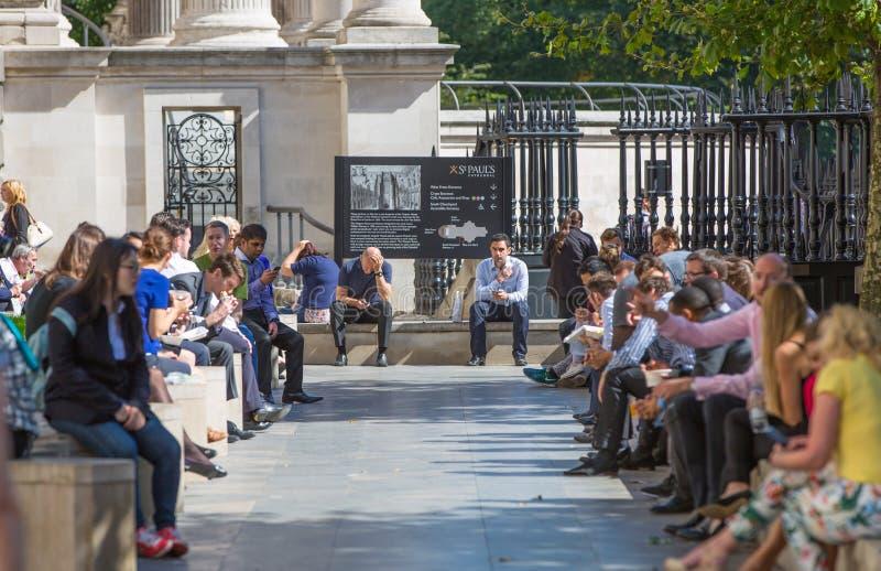 Impiegati di concetto che hanno un pranzo in parco accanto alla cattedrale di St Paul Londra, Regno Unito fotografia stock