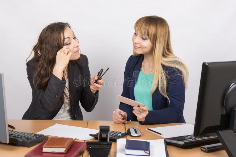 Impiegati di concetto che parlano animatamente circa i cosmetici al vostro scrittorio fotografia stock
