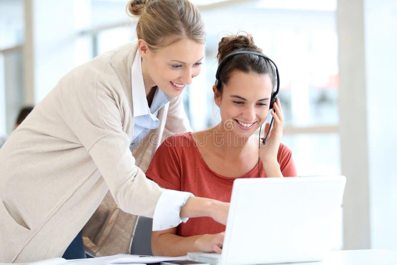 Impiegati di concetto delle giovani donne con la cuffia avricolare sul computer portatile fotografia stock libera da diritti