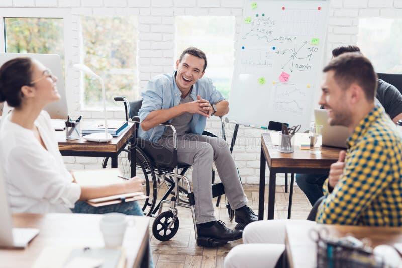 Impiegati di concetto ed uomo in una sedia a rotelle che discutono i momenti di affari in un ufficio moderno fotografie stock libere da diritti