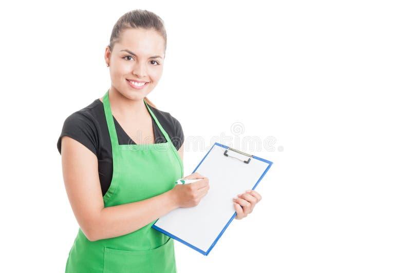 Impiegato attraente che lavora nel supermercato e che tiene lavagna per appunti immagine stock