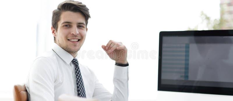 Impiegato che si siede davanti ad uno schermo di computer fotografia stock libera da diritti